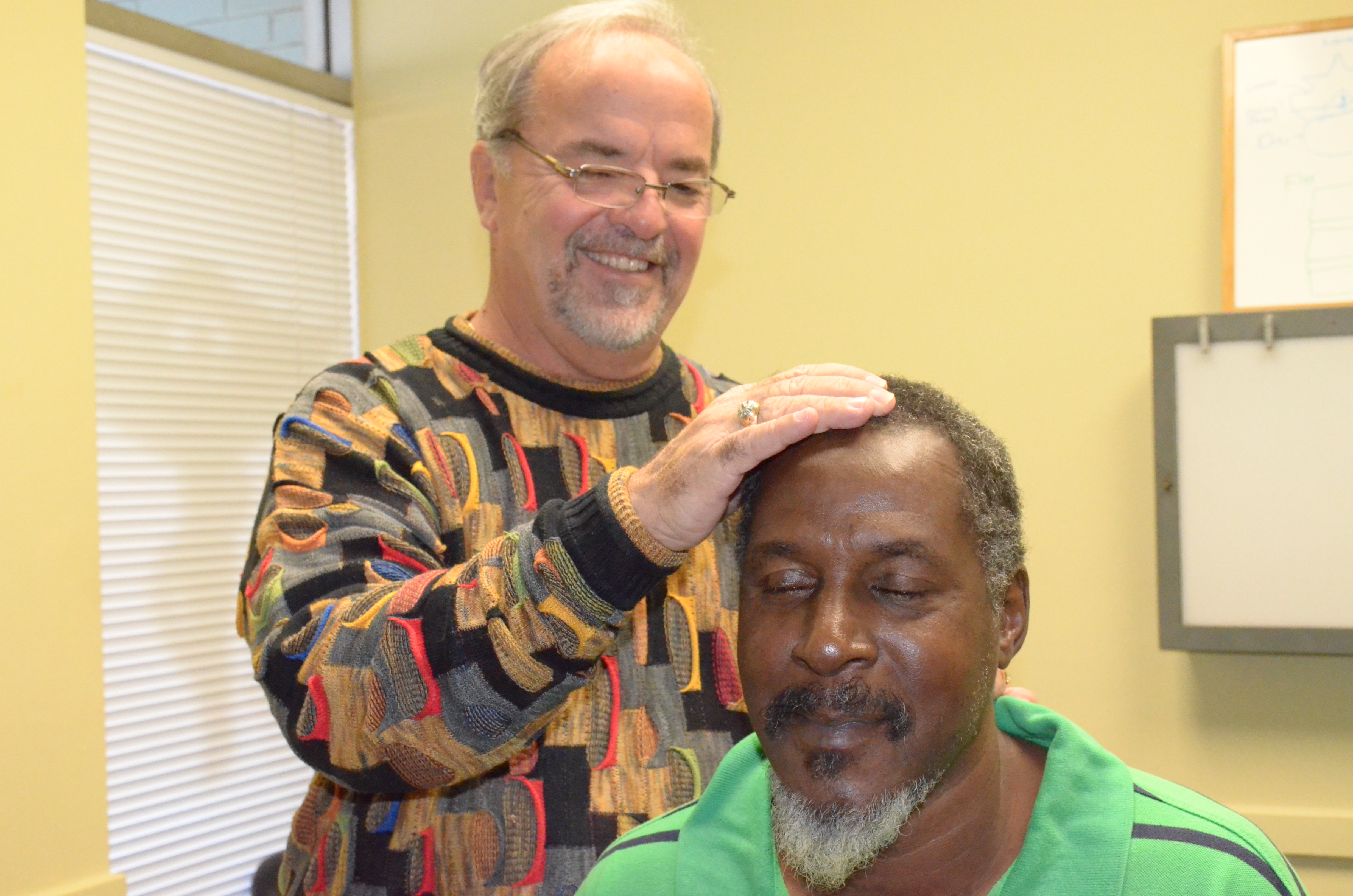 chiropractor adjusting male patient's neck