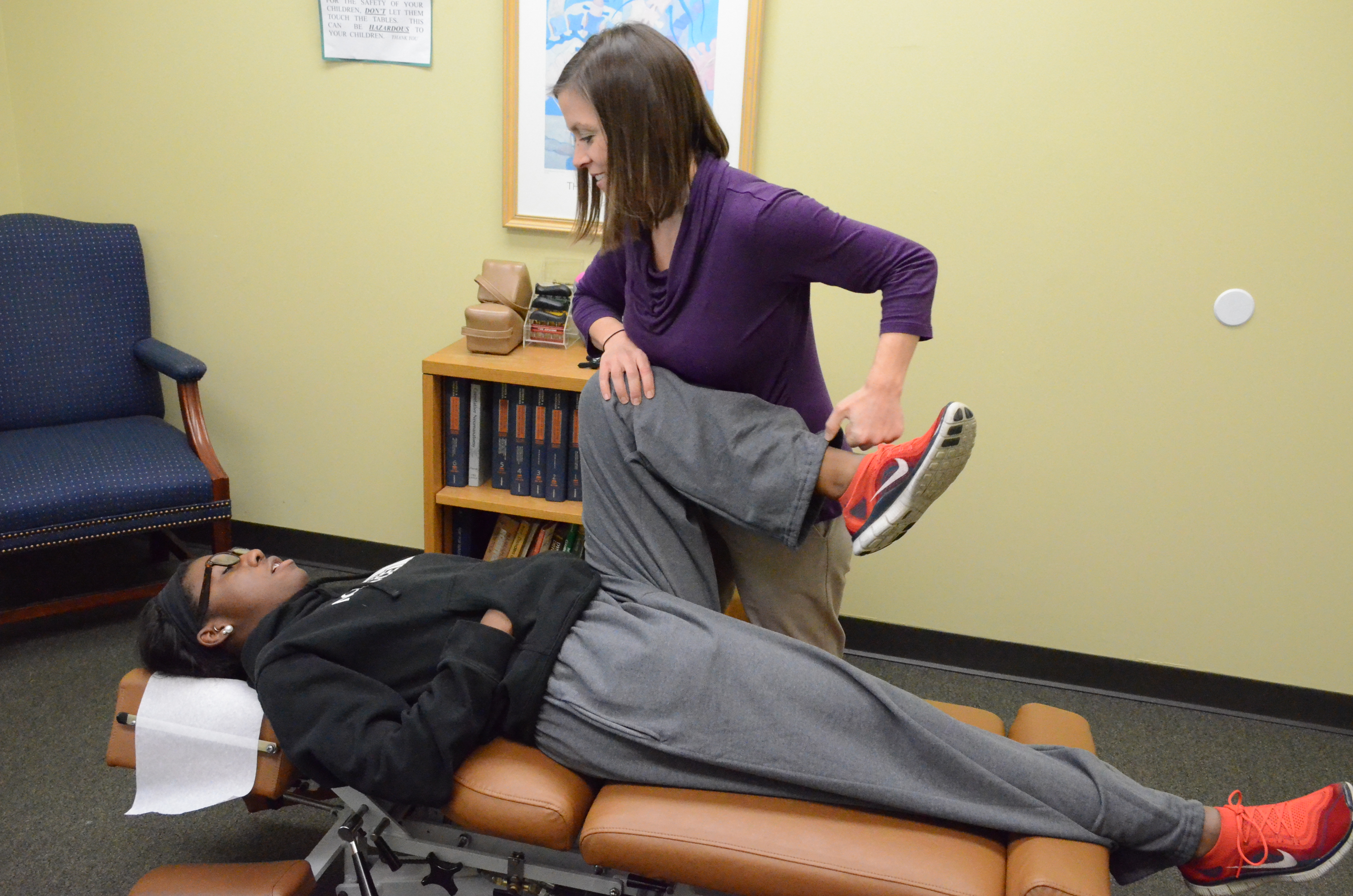 chiropractor adjusting patient's knee on table